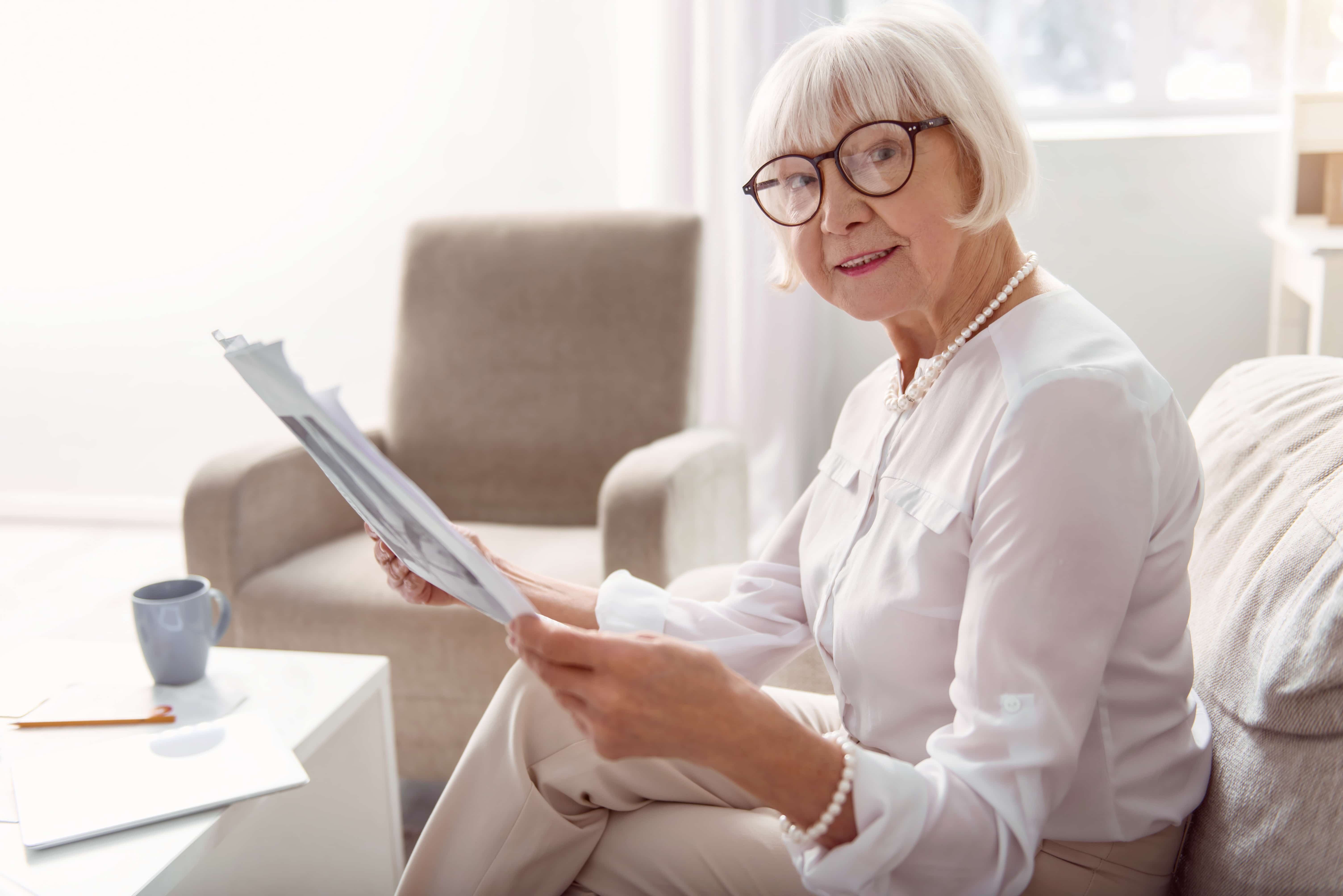 Charming senior lady posing while reading newspaper